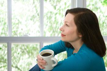 woman sitting by a window with coffee