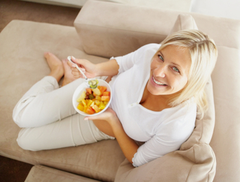 Top-down view of woman eating fruit salad